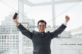 Cheerful elegant young businessman cheering in office