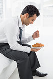Businessman sitting on bed with a plate of croissants