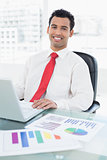 Smiling businessman with laptop and graphs sitting at office