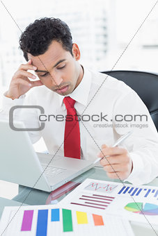Serious young businessman with laptop and graphs