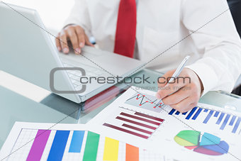 Mid section of a businessman with laptop and graphs