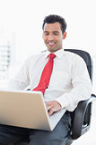 Smiling businessman using laptop at office