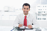 Smiling young businessman writing in diary at office