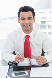 Smiling businessman writing in diary at office