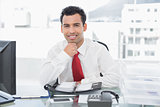 Smiling businessman with diary sitting at office