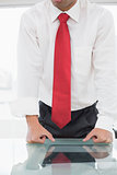 Mid section of a well dressed businessman with clenched fists on desk