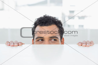 Businessman peeking behind the desk at office