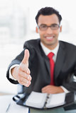 Blurred businessman offering a handshake at desk