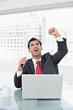 Businessman cheering in front of laptop at desk