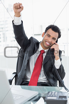 Businessman cheering while on call at office desk