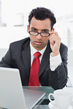 Upset businessman with laptop sitting at office desk