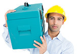 Portrait of a serious handyman in hard hat carrying a toolbox