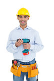 Smiling handsome young handyman in hard hat holding drill