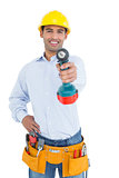 Smiling handsome young handyman holding out drill