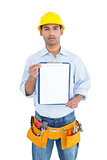 Portrait of a handyman in yellow hard hat holding a clipboard
