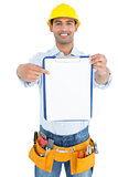 Smiling handyman in yellow hard hat pointing at clipboard