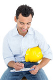 Handyman with yellow hard hat writing in clipboard