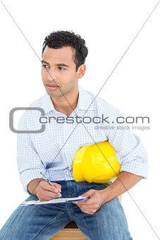 Thoughtful handyman with yellow hard hat writing in clipboard