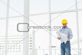 Architect in yellow hard hat looking at plans in office