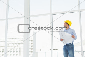 Architect in yellow hard hat with plans looking up at window