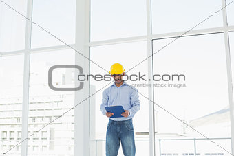 Smiling architect in yellow hard hat with clipboard in office