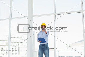 Architect in hard hat with clipboard gesturing thumbs up in office
