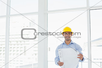 Smiling architect in yellow hard hat with blueprint in office