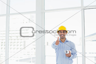 Architect in hard hat with blueprint gesturing thumbs up in office