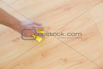 Hand with sponge cleaning the parquet floor at home