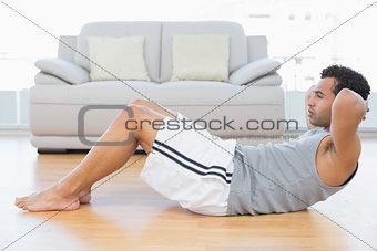 Young man doing abdominal crunches in the living room