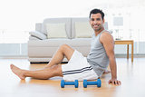 Relaxed man sitting on floor with dumbbells in the living room