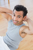 Smiling man doing abdominal crunches in the living room