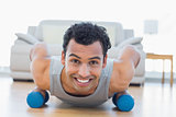 Man with dumbbells doing push ups in the living room