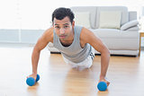 Sporty man with dumbbells doing push ups in the living room