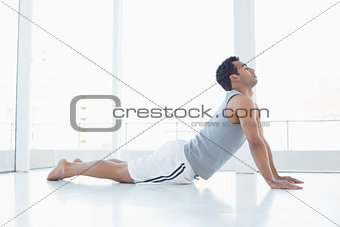 Fit young man doing the cobra pose in fitness studio