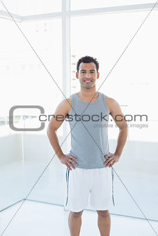 Fit man standing with hands on hips in fitness studio
