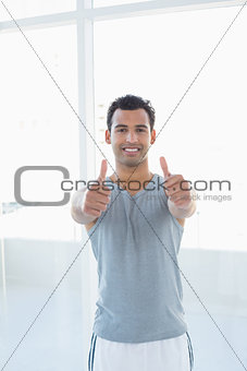 Fit young man gesturing thumbs up in fitness studio