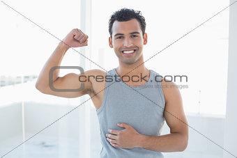 Portrait of a fit man flexing muscles in fitness studio