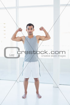 Fit young man flexing muscles in fitness studio