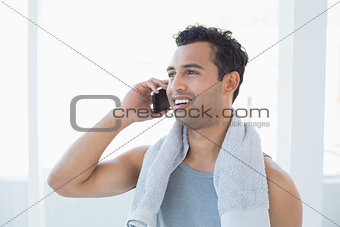 Fit young smiling man using mobile phone