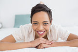 Smiling pretty young woman relaxing in bed