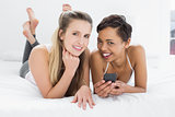 Smiling female friends with mobile phone in bed