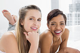 Portrait of smiling young female friends in bed