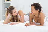 Happy young female friends lying in bed