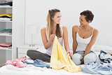 Two female friends selecting clothes in bed
