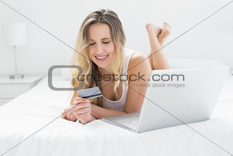 Casual young woman doing online shopping in bed