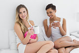 Portrait of female friends with coffee cups in bed