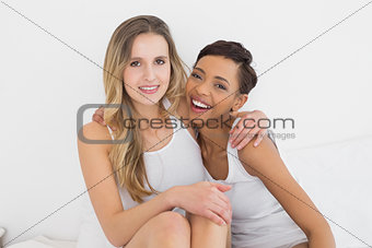 Portrait of young female friends sitting on bed