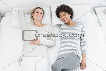 Portrait of casual female friends lying in bed