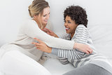 Relaxed female friends enjoying a conversation in bed